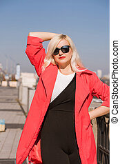 Lovely blonde model posing in red cloak, wears sunglasses on a blurred city background