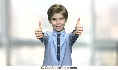 Lovely boy giving two thumbs up.