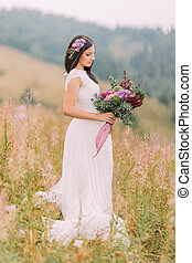 Lovely brunette bride standing with bouquet on the field in Alpian mountains