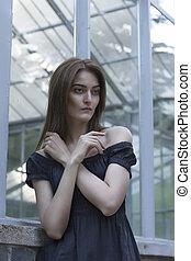 Lovely brunette model in dress at the window