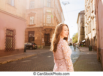 Lovely brunette model in lace dress posing with closed eyes at the city street