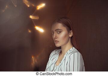 Lovely brunette model posing in the dark room with lights