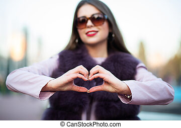 Lovely brunette model wearing sunglasses showing heart symbol with two hands over a city background