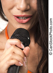 Impassioned woman in orange shirt with microphone.