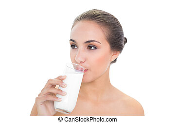 Lovely brunette woman drinking a glass of milk