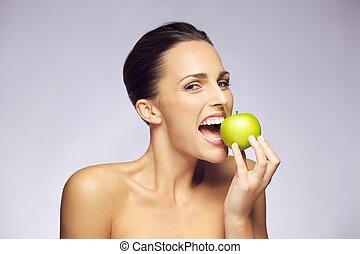 Lovely brunette woman eating fresh green apple