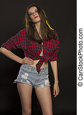 Lovely brunette woman in jeans shorts and a plaid shirt