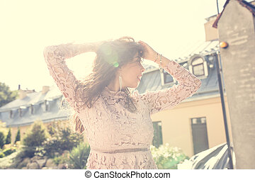 Lovely brunette woman in lace dress posing at the street in rays of sun