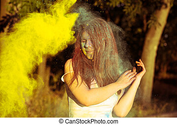 Lovely brunette woman in the city park playing with colorful Holi powder