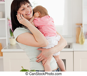 Lovely brunette woman on the phone while holding her baby in her arms in the kitchen