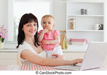 Lovely brunette woman relaxing with her laptop next to her baby while sitting in the kitchen