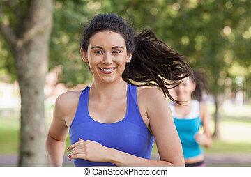 Lovely brunette woman running in a park