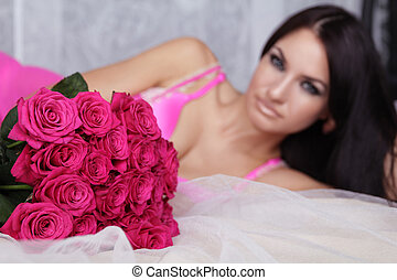 Lovely brunette woman with bouquet of pink roses lying on the bed.