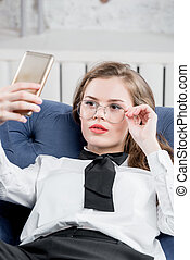 Lovely businesswoman with a phone in glasses