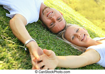 Lovely Caucasian Couple Smiling And Relax On Grass
