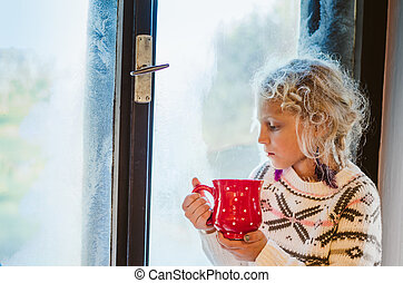 lovely child drinking tea by the window