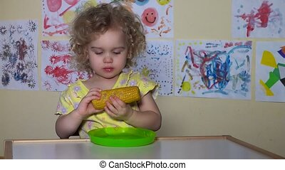 Lovely child girl eating a boiled corn cob. Static closeup...