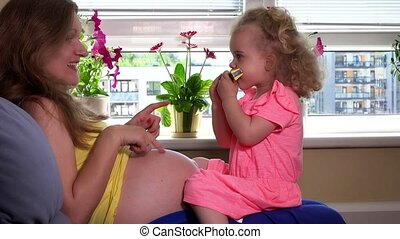 Lovely child girl play with mouth organ sitting on pregnant mother knees