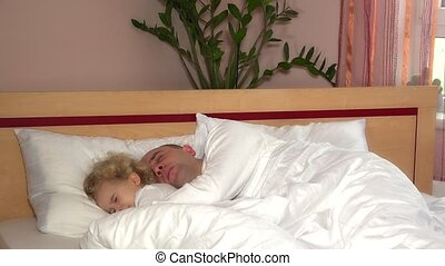 Lovely child girl with bald head man father wake up in...