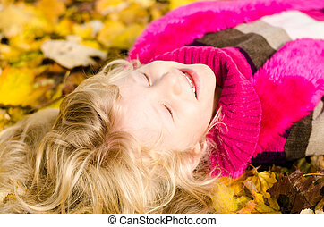 lovely child in autumn leaves