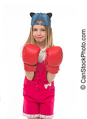 Lovely child wearing huge red boxing gloves. Girl in pink overalls isolated on white background. Kid wearing cute cap with animal ears backwards. Little fighter on training, self defence concept