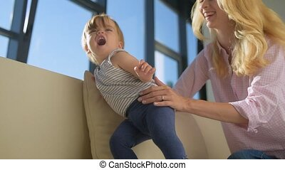 Lovely child with pleasant mother on the sofa