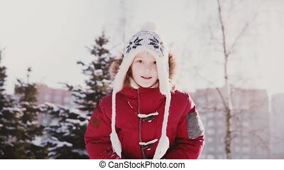 Lovely close-up portrait of cute little Caucasian girl in winter clothes throwing snow in the air having fun slow motion