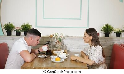 lovely couple eating cakes in confectionery shop