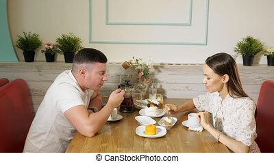 lovely couple eats natural cakes at table in sweet shop