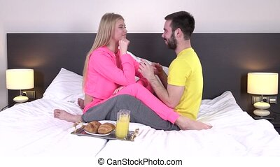 Lovely couple having breakfast in their bed at home, closeup