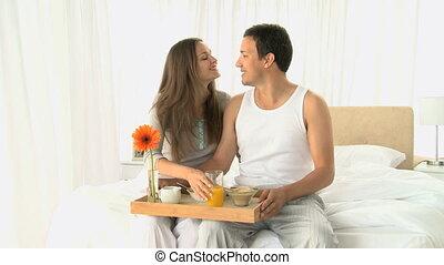 Lovely couple having breakfast sitt