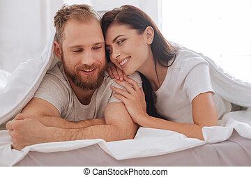 Lovely couple having pillow talk underneath blanket