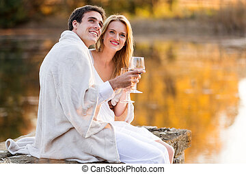 lovely couple having wine by the lake