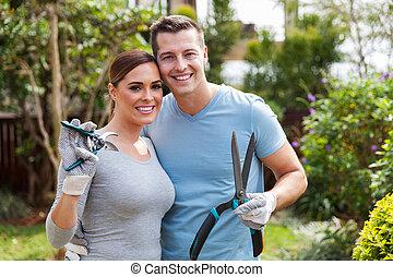 couple holding gardening tools