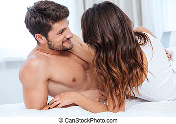 Lovely couple hugging on their bed at home - Lovely...
