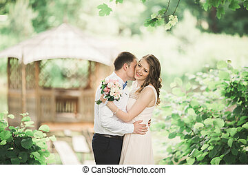 Lovely couple in love kissing each other on the day wedding, standing in the park outdoors near lake