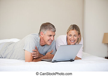 Lovely couple looking at their laptop