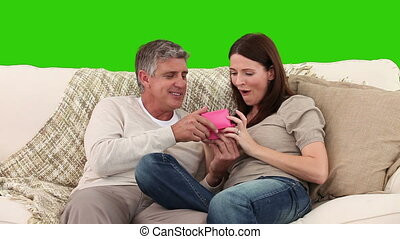 Lovely couple opening some gifts on a sofa - Chromakey...