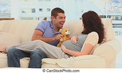 Lovely couple playing with a teddy