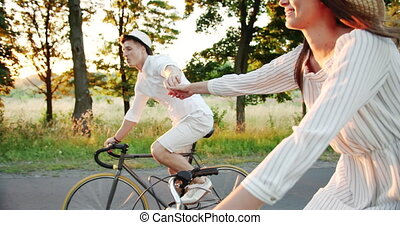 Lovely Couple Riding Bicycles and Holding Hands