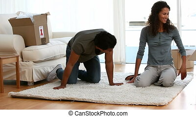 Lovely couple rolling a carpet