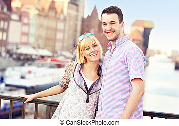 A picture of a young couple posing to the camera in the city