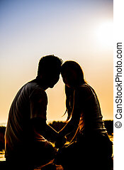 Lovely Couple sit in the sunset with silhouette scene