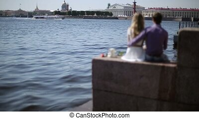 Lovely couple sitting on embankment at sunny day