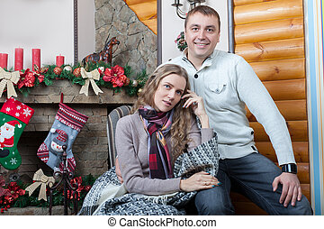 Lovely couple sitting on the chair near fireplace