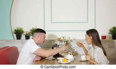 lovely couple spends time eating cakes in confectionery shop
