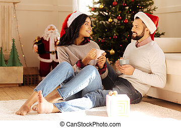 Lovely couple talking while drinking coffee on Christmas