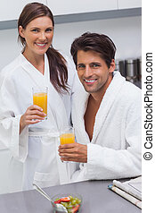 Lovely couple wearing bathrobes and holding glass of orange juice in the kitchen