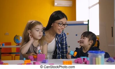 Lovely diverse girls enjoying playtime in classroom - Two...