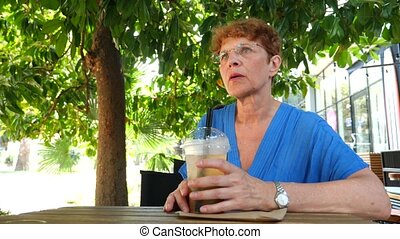 Lovely elderly woman is walking in the city park. She drinks...